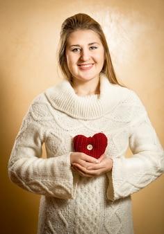 Bella donna sorridente che tiene grande cuore a maglia rosso