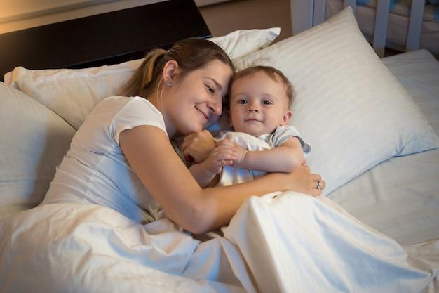 Bella donna sorridente sdraiata a letto di notte e abbracciando il suo bambino