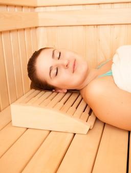 Bella donna sorridente sdraiata sulla panchina in sauna
