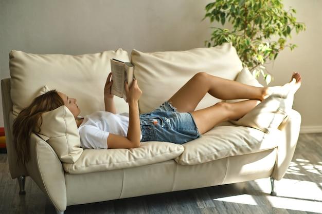 Bella donna sorridente che legge un libro a casa