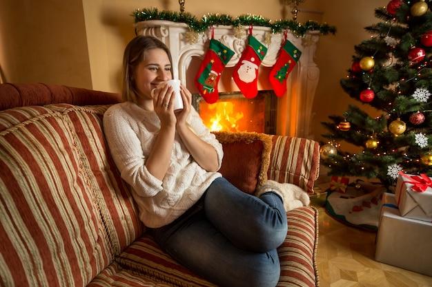 Bella donna sorridente che si rilassa al caminetto e beve il tè
