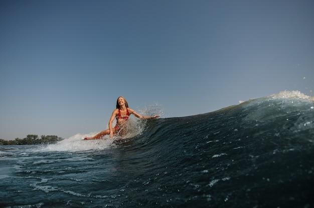 Bella donna sorridente che pratica il surfing su un'onda blu alta