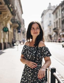 Bella donna sorridente che cammina sulla strada affollata della città dal lavoro