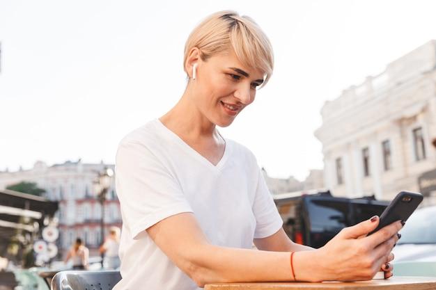 Bella donna sorridente che indossa una maglietta bianca utilizzando il telefono cellulare e gli auricolari wireless, mentre è seduto al bar all'aperto in estate e beve caffè dal bicchiere di carta