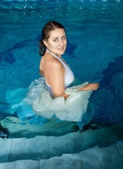 Bella donna sorridente in abito bianco che cammina in piscina