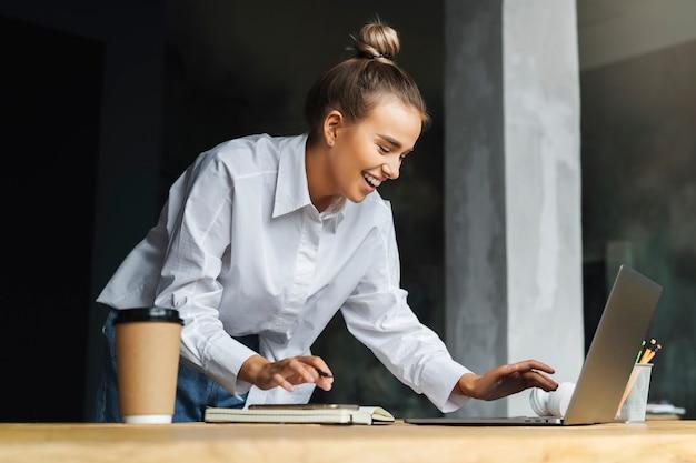 Bella donna sorridente in camicia bianca lavora davanti al computer portatile.