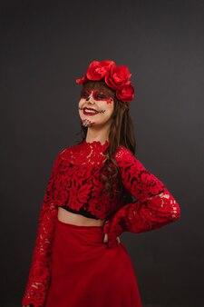 Bella donna sorridente con il trucco e l'abbigliamento dia de los muertos su sfondo nero.