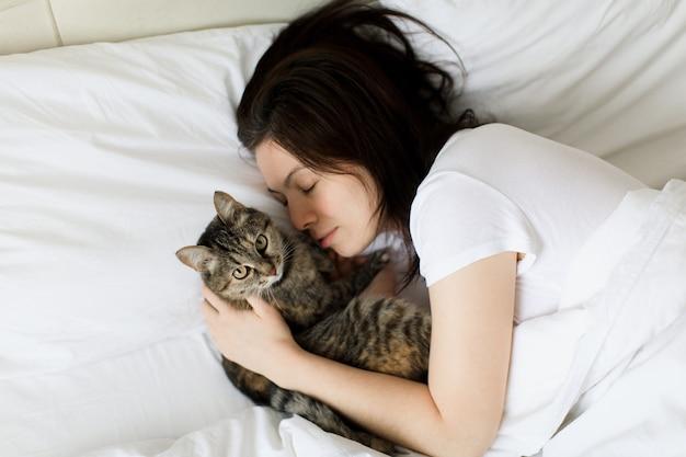 Bella donna sorridente con gli occhi chiusi sdraiata a letto e abbracciando il gatto