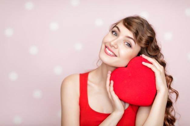 Bella donna sorridente con cuori rossi per il giorno di san valentino