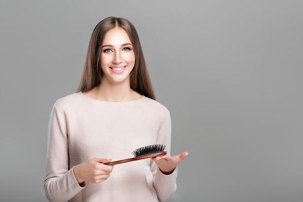 La bella donna sorridente con capelli naturali lunghi e lisci tiene la spazzola per capelli