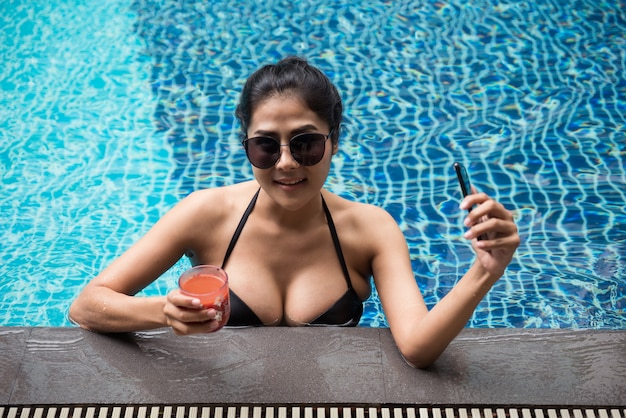 La bella giovane donna asiatica sorridente in bikini e occhiali da sole beve succo di pomodoro e tiene lo smartphone in piscina. vacanziere e vacanze estive in un paese tropicale.