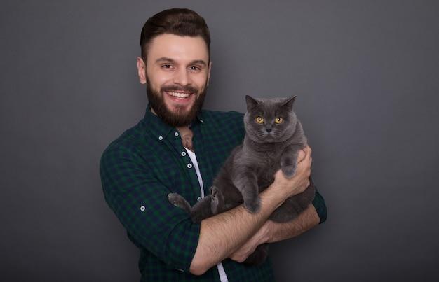 Bello giovane uomo barbuto sorridente tiene il suo adorabile gatto soffice sulle mani e posa insieme come migliori amici