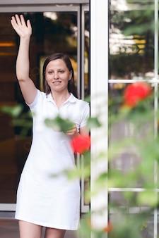 Una bella giovane donna bionda sorridente in un abito bianco incontra o accompagna i suoi amati ospiti o il suo amato fidanzato, parenti o un ristorante. alla porta di casa tua o al ristorante caffetteria.