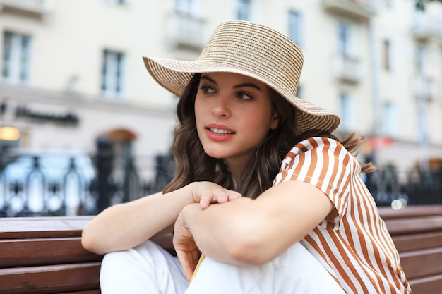 Bella giovane donna castana sorridente che si siede sul banco in parco.