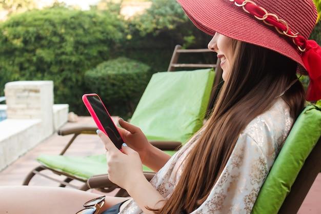 Bella ragazza sorridente che usa il suo smartphone nel suo cortile.