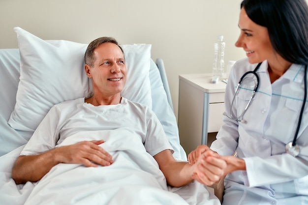 Una bella e giovane infermiera sorridente controlla il polso sul braccio di un paziente maturo che giace su un letto in un reparto moderno.