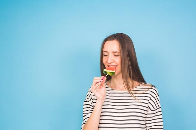 Bella giovane donna sorridente che tiene fetta di anguria sul bastone su sfondo blu