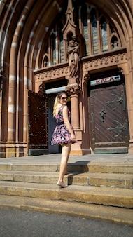 Bella giovane donna sorridente in posa su vecchie scale di pietra contro la cattedrale cattolica nella città vecchia