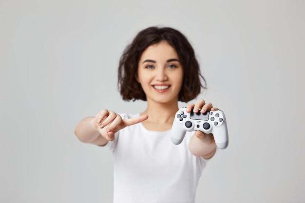Bella giovane donna sorridente che mostra alla console per videogiochi. concentrati sulla console