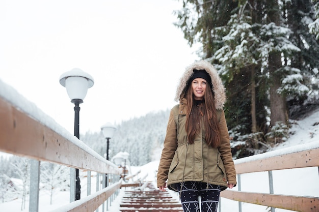 Bella giovane donna sorridente che cammina sulle scale nel resort di montagna invernale