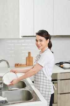 Bella giovane donna sorridente che lava i piatti in cucina bianca moderna.