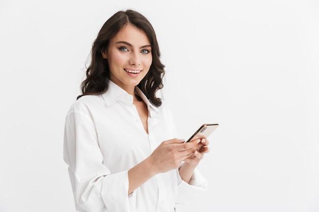 Bella giovane donna sorridente con lunghi capelli castani ricci che indossa una camicia bianca in piedi isolata sul muro bianco, usando il telefono cellulare