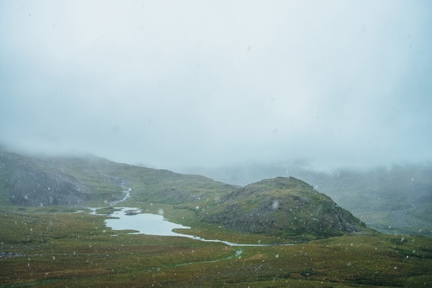 Bella nevicata con grandi fiocchi di neve in alta montagna. lago di montagna tra le colline durante la nevicata. paesaggio panoramico con fiocchi di neve. atmosferico scenario alpino con nevicate negli altopiani.