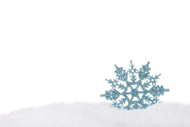 Bellissimo fiocco di neve nella neve isolato su bianco