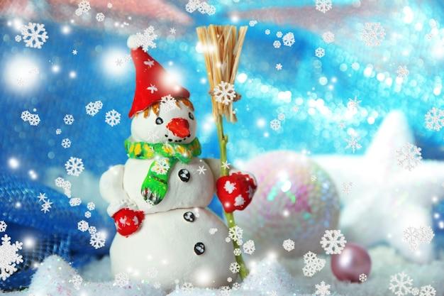 Bellissimo pupazzo di neve e decorazioni natalizie, su sfondo luminoso
