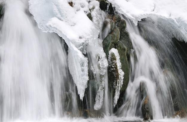 Bella cascata nevosa che scorre in montagna