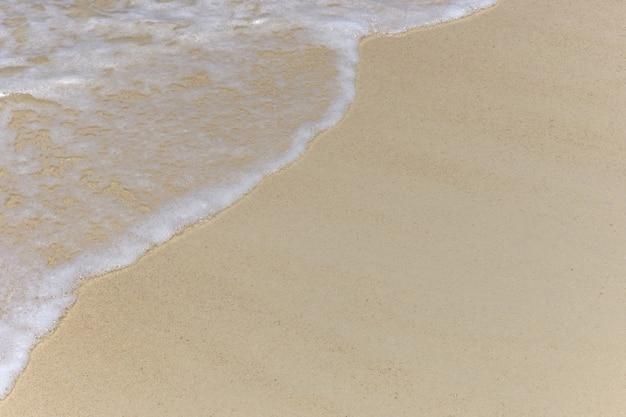 Bella morbida onda del mare sul fondo di struttura della spiaggia sabbiosa pulita
