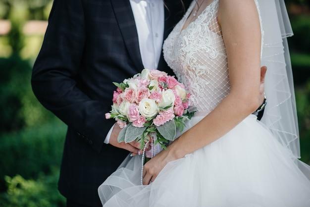 Il primo piano bello e sofisticato del mazzo di nozze tiene la sposa in sue mani vicino allo sposo. bouquet da sposa e anelli.