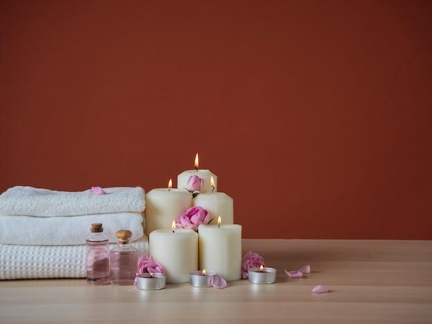 Bella composizione spa con candele profumate accese e olio aromatico, rose rosa sul tavolo di legno