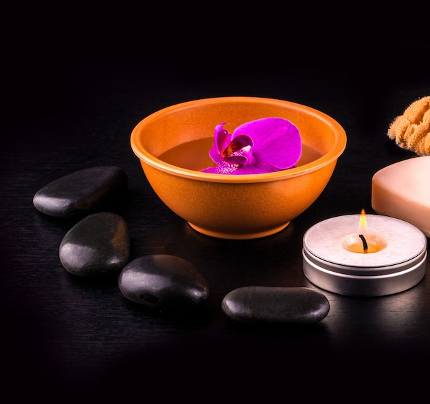 La bellissima composizione spa con orchidea rosa sulla tazza, pietre e guanti bianchi sulla tavola di legno nera