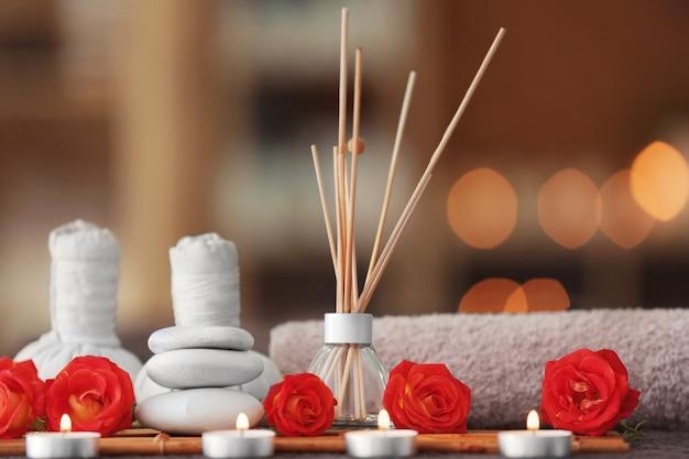 Bella composizione spa con deodorante per canne e candele su sfondo sfocato