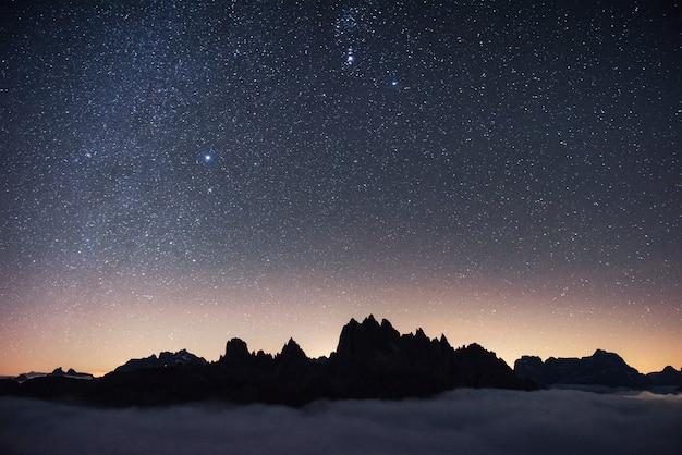 Bellissimo spazio pieno di stelle nel cielo. le montagne sono circondate da una fitta nebbia.