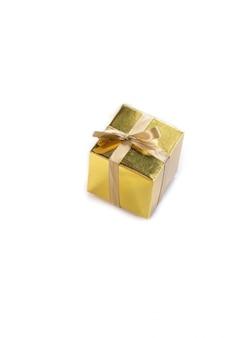 Presente o sorpresa isolato bello contenitore di regalo dorato scintillante con il bello spazio dell'arco per testo