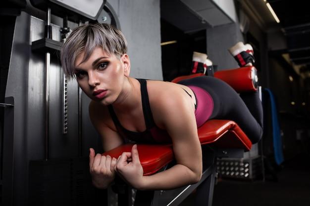 Bella ragazza sportiva è impegnata su un simulatore in palestra. bella ragazza con la bella figura stretta. ragazza fitness in palestra