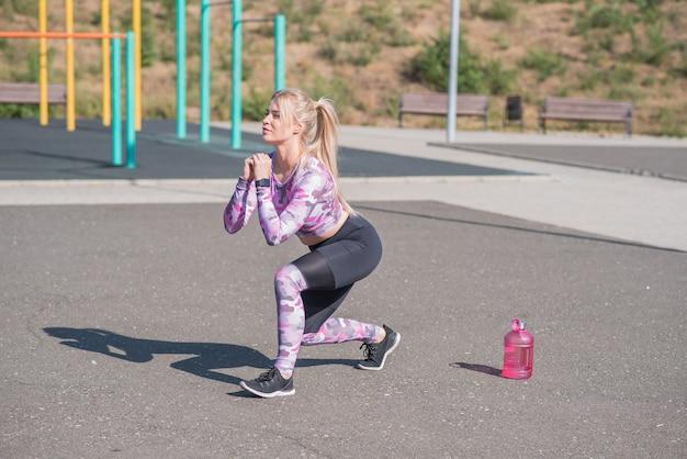 Bella e sportiva ragazza bionda facendo affondi su un campo sportivo di strada