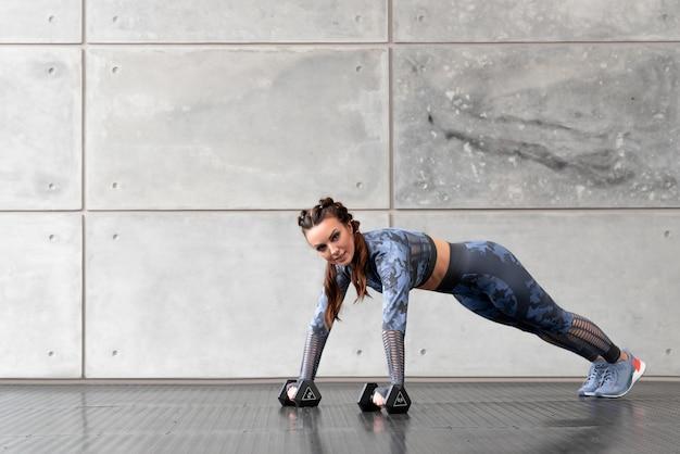 Bella ragazza sportiva con le trecce fa flessioni con manubri in mano sullo sfondo di un muro grigio. tuta mimetica blu. sport e salute