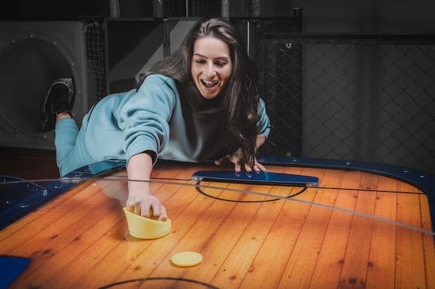 Bella ragazza sportiva gioca ad air hockey nel centro di intrattenimento