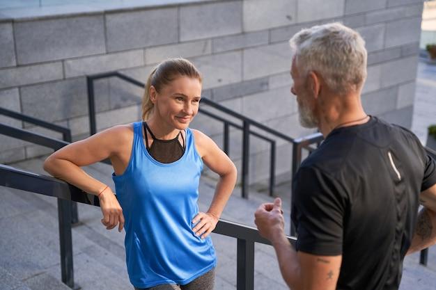 Bella sportiva che sorride mentre parla con il marito o l'amica in piedi all'aperto dopo