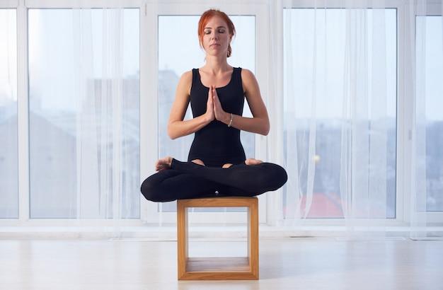 La bella donna sportiva adatta pratica l'asana padmasana di yoga