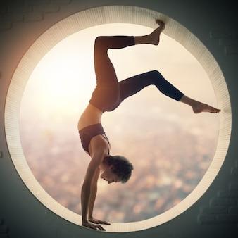 La bella donna yogi in forma sportiva pratica il handstand di yoga asana bhuja vrischikasana - la posa dello scorpione in una finestra