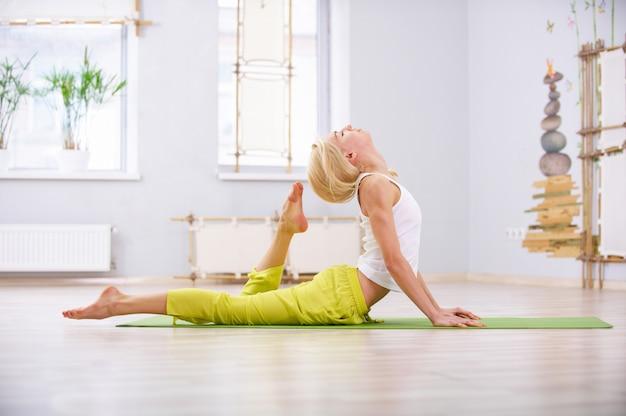 La bella donna yogi in forma sportiva pratica yoga sdraiato asana ardha bhujangasana nella sala fitness