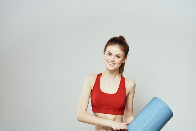 Bella ragazza sportiva in posa contro il muro bianco