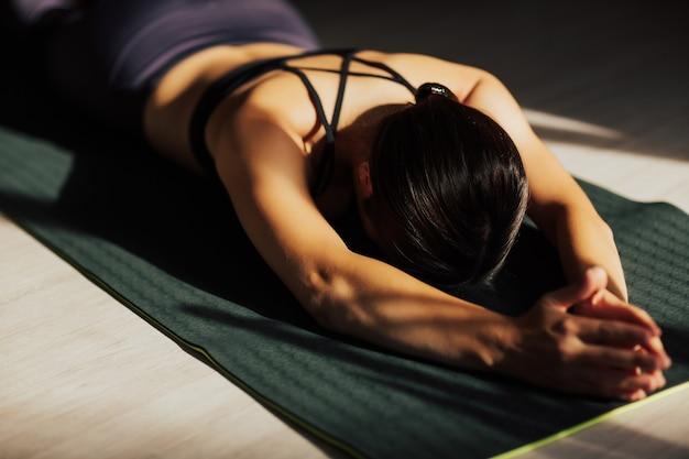 Bella donna sportiva che si esercita a casa, facendo yoga per la colonna vertebrale sul pavimento, sdraiato e riposando dopo l'allenamento.