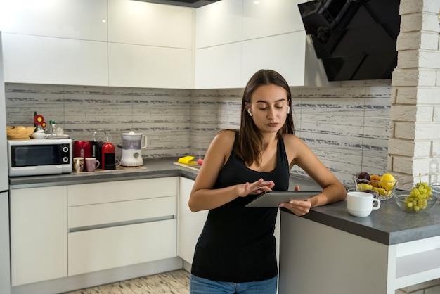 Bella donna sportiva ascolta musica e guarda il suo tablet in cucina. il concetto di un weekend perfetto