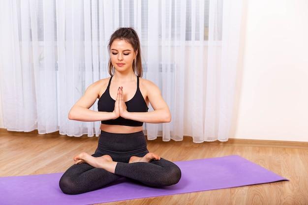 Bella donna sportiva pratica asana yoga a casa