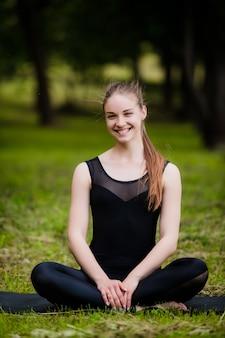 Bella giovane donna sportiva che risolve sulla stuoia nera